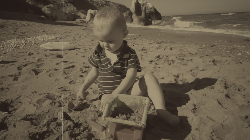 Child playing with toys in sand on the beach. Vintage black and white film with grain, noise and scratches Royalty-Free Stock Footage #1066032943