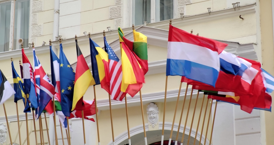 Multiple various flags of the world, blowing in the wind, with an old architectural style building in the background. | Shutterstock HD Video #1066035385