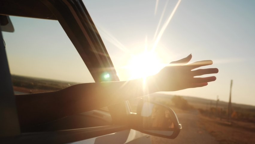 Free girl hand out of the window rides a car wind in the face. concept car travel on the road. girl stretches her hand out of the car window sun glare sunset. movement driver hand out of the window