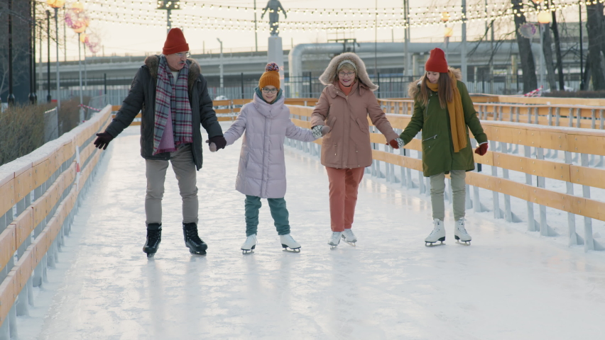 Full shot of young girl skating on outdoor ice rink with mother and grandparents having good time together at sunset | Shutterstock HD Video #1066052353