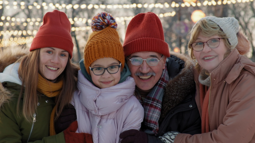 Medium close-up portrait of cheerful family in winter clothing spending good time at ice rink smiling to camera | Shutterstock HD Video #1066053028