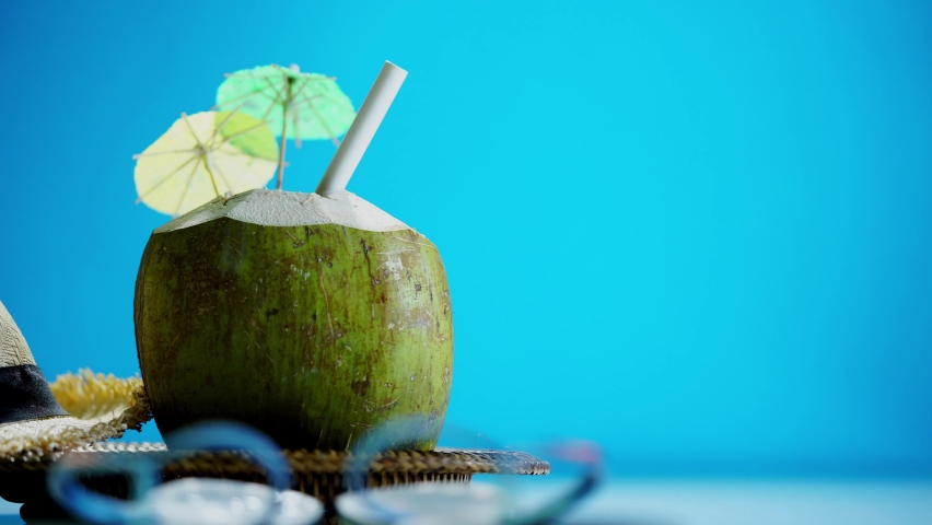 Straw head and fresh young coconut with straw and little umbrella ready for drink. Tropical vacation travel concept | Shutterstock HD Video #1066053664