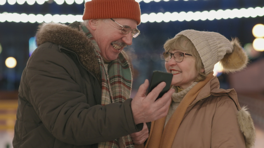 Chest-up shot of laughing caucasian senior couple taking selfie on smartphone while ice-skating in winter on open-air ice rink | Shutterstock HD Video #1066054207