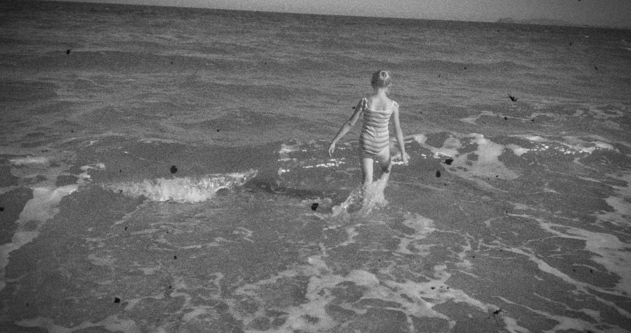Happy girl on the beach playing with waves. Vintage black and white film Royalty-Free Stock Footage #1066054642