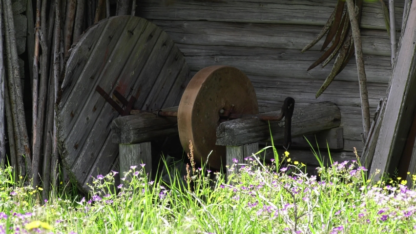 Old grindstone on a farm with colorful flowers in the foreground. Small insects flying in peaceful farm setting | Shutterstock HD Video #1066054720