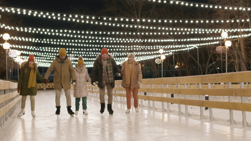 Full shot of multi-generational caucasian family of five having fun together skating on ice rink outdoors holding hands on cold winter evening | Shutterstock HD Video #1066055452