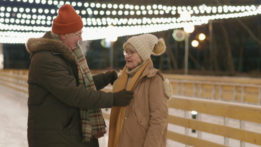 Tilting-down close-up of happy elderly couple ice-skating on rink outdoors holding hands in winter | Shutterstock HD Video #1066055617