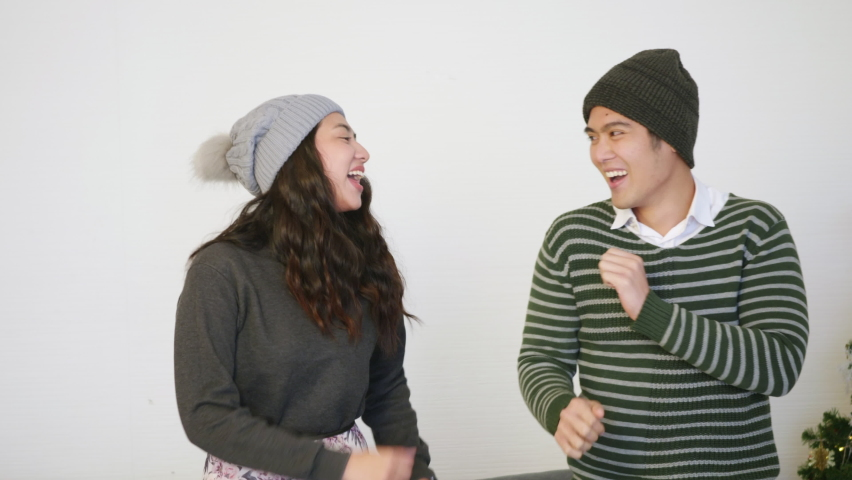 Happy Asian beautiful young family couple lifestyle husband and wife smile dancing laughing around christmas tree at home living room, man and woman are enjoying spending time together, slow motion | Shutterstock HD Video #1066055674