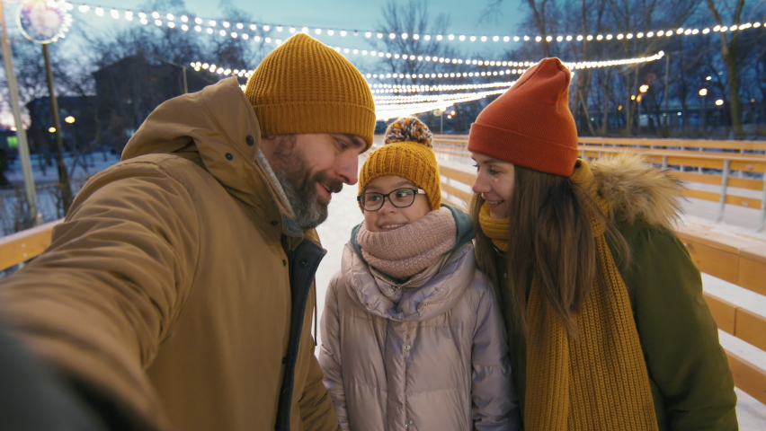 Pov close-up of young happy family taking selfie while ice-skating on winter evening at outdoor ice rink | Shutterstock HD Video #1066055941
