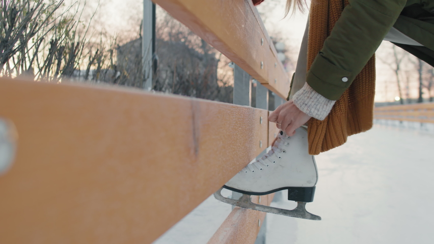 Close-up of unrecognizable woman tying laces on her white figure skate outdoors in winter | Shutterstock HD Video #1066056316