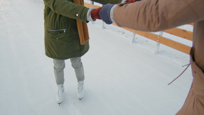 Handheld tracking medium close-up of pretty woman in winter clothes taking skating lessons with boyfriend teaching her at ice rink outdoors | Shutterstock HD Video #1066058908