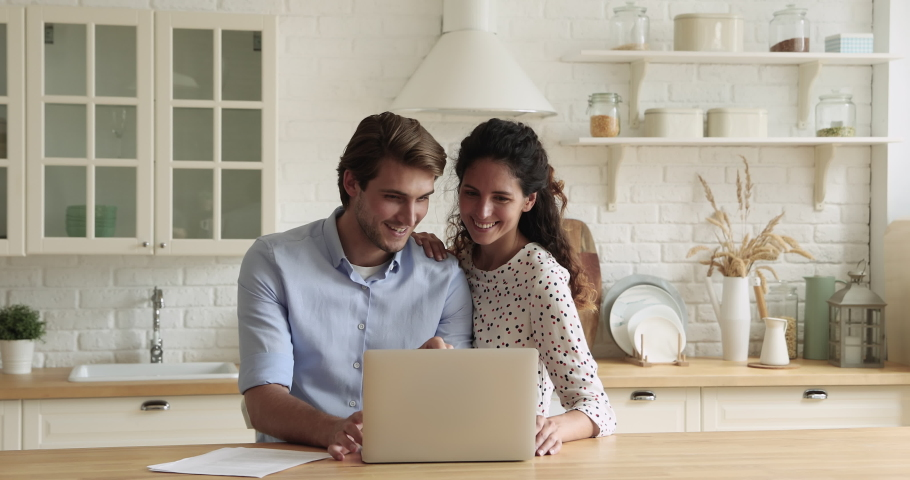 Bonding millennial smiling couple looking at laptop screen, choosing goods in online store involved in internet shopping, discussing planning vacation trip booking hotel or flight tickets on computer. Royalty-Free Stock Footage #1066095907