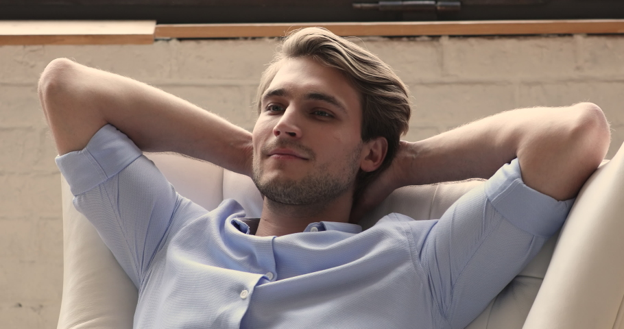 Head shot close up relaxed young handsome businessman daydreaming sleeping with folded hands behind head in comfortable armchair, enjoying peaceful stress free moment after finishing job indoors.   Shutterstock HD Video #1066096009