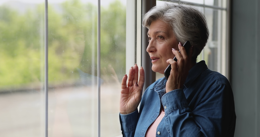 Middle-aged grey-haired woman standing near panoramic window at home holds mobile phone talking. Older generation and modern tech usage, phonecall activity, make order, communication distantly concept