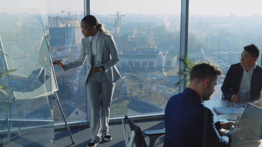 Multi-Ethnic Corporate Staff Listening to Sales Seminar by Afro-American Boss Businesswoman Negotiating inside Corporate Boardroom. Meeting. Brainstorming. Royalty-Free Stock Footage #1066102474