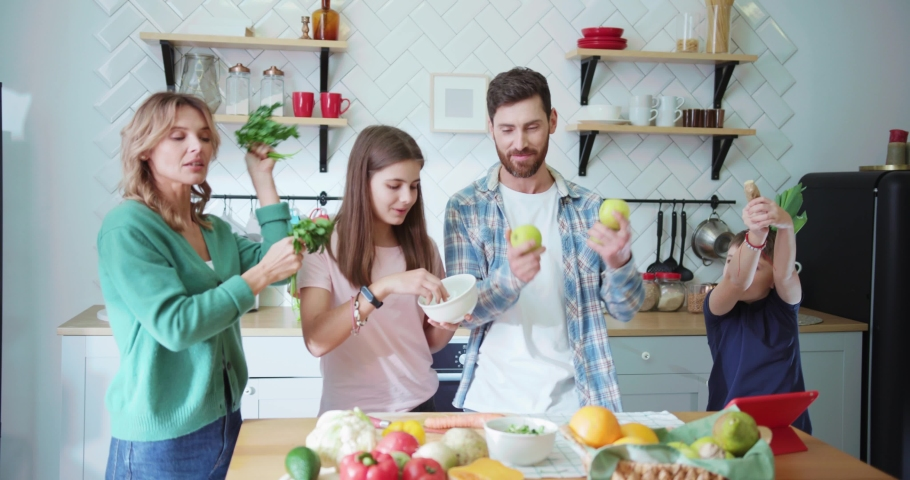 NEW YORK - 19 May 2018: Excited parents with their teen kids dancing in middle of kitchen having fun cooking breakfast lunch together. Home entertainment. Food preparation.