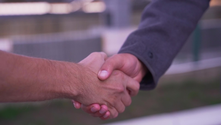 Two men shaking hands greeting each other on the street. Securing a business deal with a handshake.  Close up video shot of men shaking hands. Two colleagues greeting each other with a handshake.