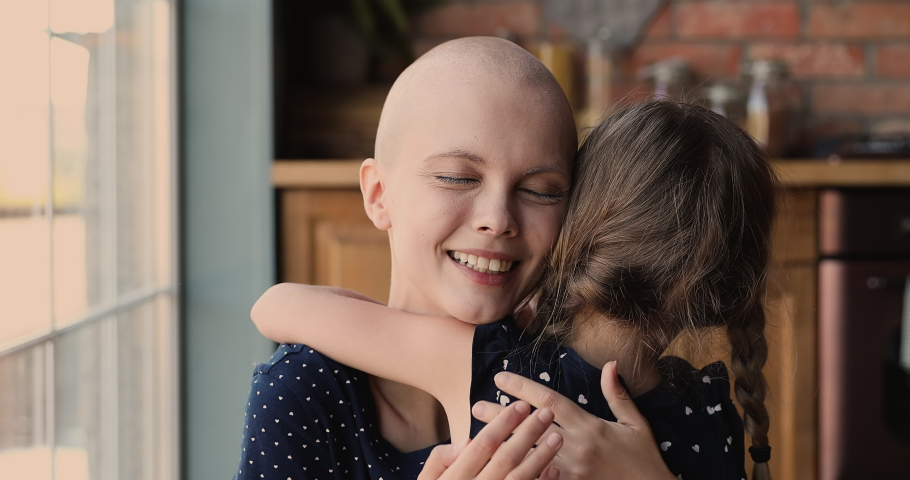 Close up young female bald cancer patient loving mom cuddling her little daughter feeling love receive support, kid rear back view, meaning of live, motivation for oncology disease struggle concept