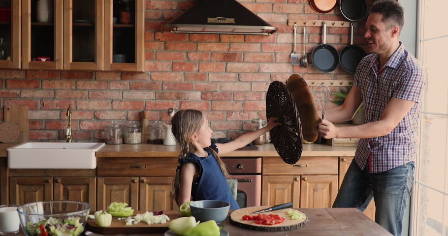 Happy little cute daughter play active game with dad in kitchen, holding kitchenware fighting laughing enjoy funny quarantine playtime together indoor. Leisure, activity with kids at home, fun concept