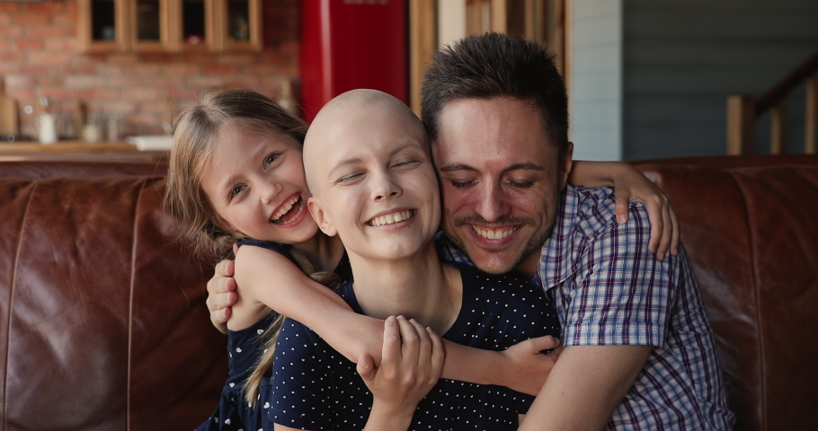 Loving husband, cheerful little daughter hugging young bald female mother wife cancer patient. Happy family celebrate recovery, victory over oncology disease sitting on couch at home feels overjoyed