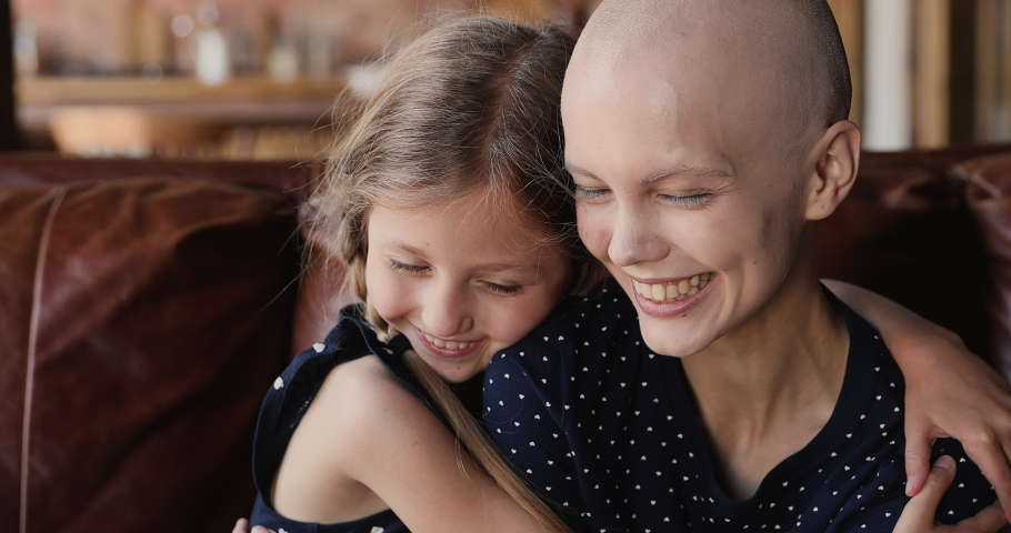 Close up little daughter hugs mother cancer patient. Happy family sit indoor embracing feeling grateful for remission, express love, kid girl supporting mom, encourage her, hoping in recovery concept Royalty-Free Stock Footage #1066121212