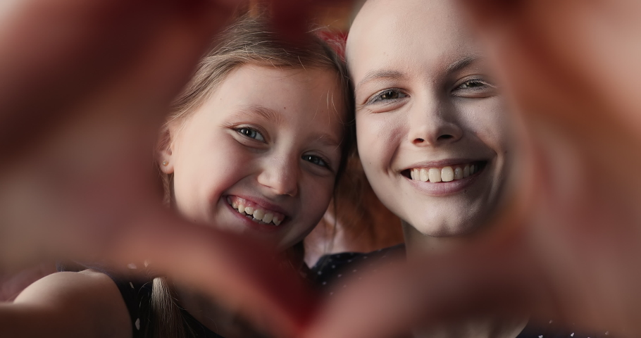 Little adorable girl her young bald mother making heart shape with hands showing symbol of love at camera, close up view happy faces. Share support optimism and hope with other cancer patients concept
