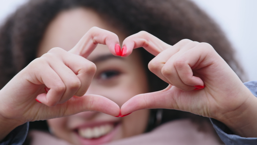 Close-up of female fingers with dark skin and manicure showing shape of heart, Afro American defocused woman demonstrating love affection sympathy symbol makes peace support gesture, focus on hands Royalty-Free Stock Footage #1066122835