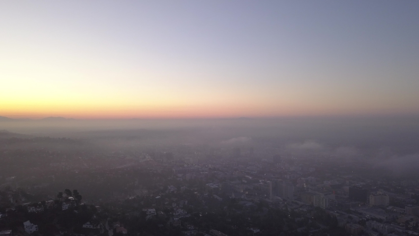 Fog and Clouds over Hollywood Hills at Sunrise with view above Los Angeles, California, Aerial Wide Angle tilt down Shot | Shutterstock HD Video #1066128262