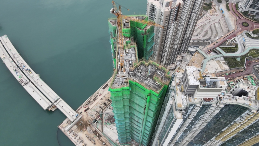 Large-scale commercial and residential construction site works Cranes Foundation works in Lohas Park, Tseung Kwan O of Hong Kong city, Kowloon Aerial Top view | Shutterstock HD Video #1066141372