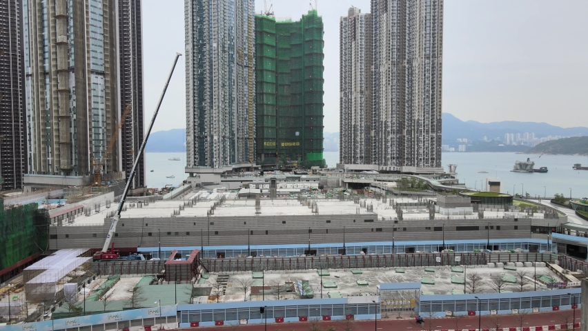 Large-scale commercial and residential construction site works Cranes Foundation works in Lohas Park, Tseung Kwan O of Hong Kong city, Kowloon Aerial Top view | Shutterstock HD Video #1066141375