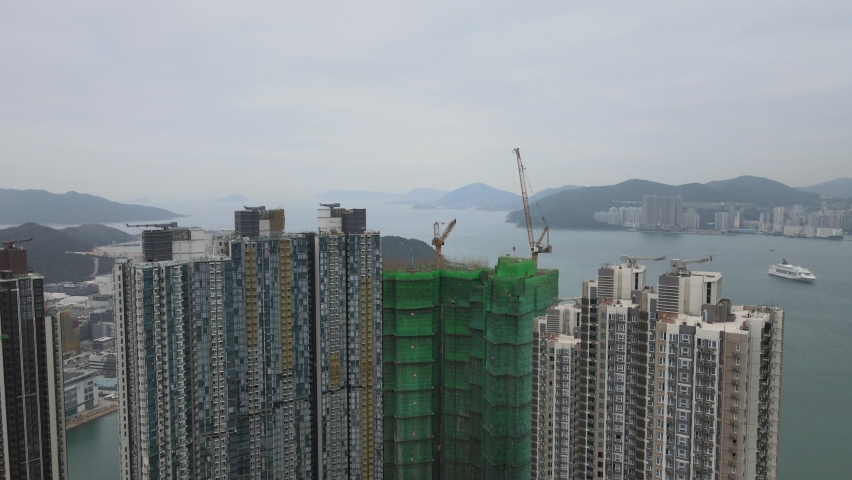 Large-scale commercial and residential construction site works Cranes Foundation works in Lohas Park, Tseung Kwan O of Hong Kong city, Kowloon Aerial Top view | Shutterstock HD Video #1066141387