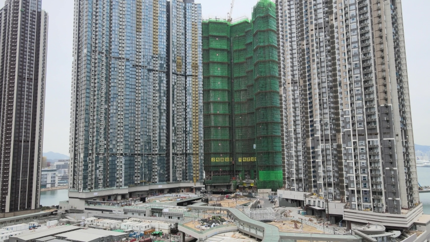 Large-scale commercial and residential construction site works Cranes Foundation works in Lohas Park, Tseung Kwan O of Hong Kong city, Kowloon Aerial Top view | Shutterstock HD Video #1066141399