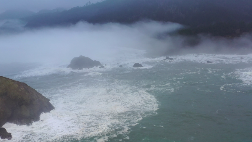 The marine layer drifts over sea stacks and the beautiful Northern California coastline in Klamath. The scenic Pacific Coast Highway runs along this amazing part of the west coast. Royalty-Free Stock Footage #1066147387