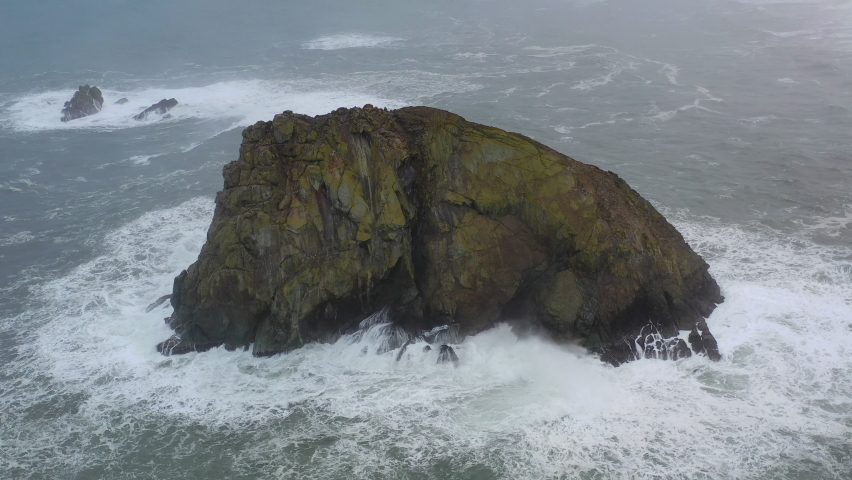 The cold waters of the Pacific Ocean wash against sea stacks and the rocky Northern California coastline in Klamath. The scenic Pacific Coast Highway runs along this amazing part of the west coast. Royalty-Free Stock Footage #1066147390