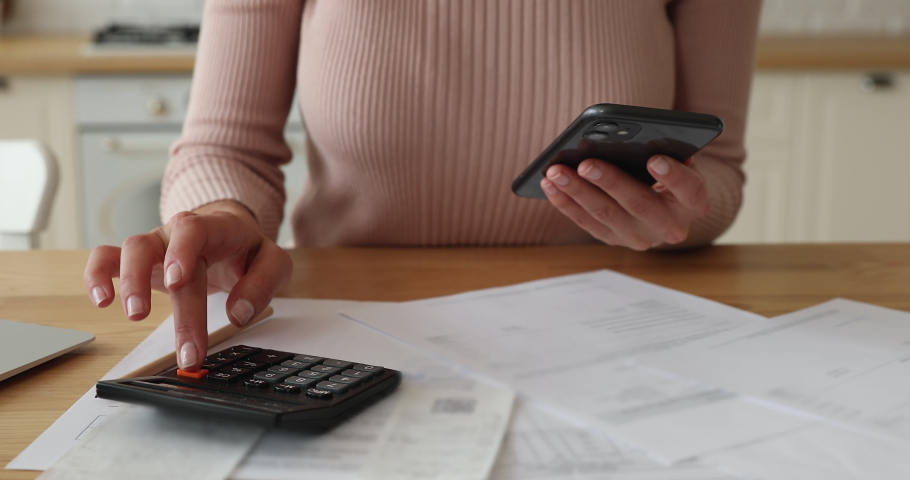 Close up young woman calculating domestic utility bills, making payment online in cellphone e-banking application, managing expenditures or monthly budget, modern technology easy usage concept. Royalty-Free Stock Footage #1066149766