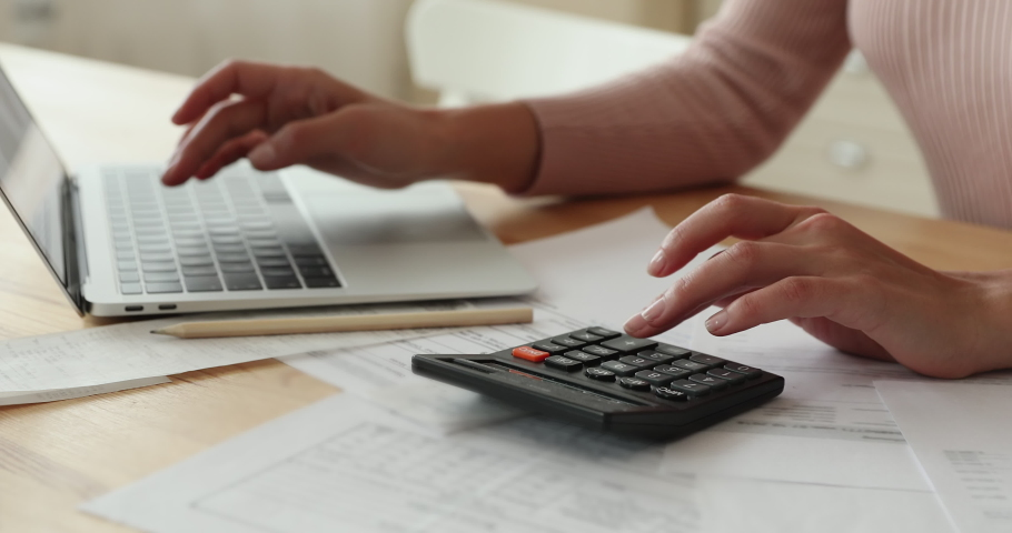 Close up young smart woman involved in financial domestic routine managing monthly budget, calculating taxes or summarizing bills, paying for utilities online in e-banking computer application. Royalty-Free Stock Footage #1066149775