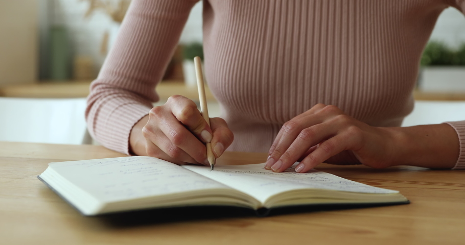 Close up young successful businesswoman planning workday or meetings, writing tasks in paper planner. Focused female student studying, making notes in copybook, sitting at wooden table at home. Royalty-Free Stock Footage #1066149808