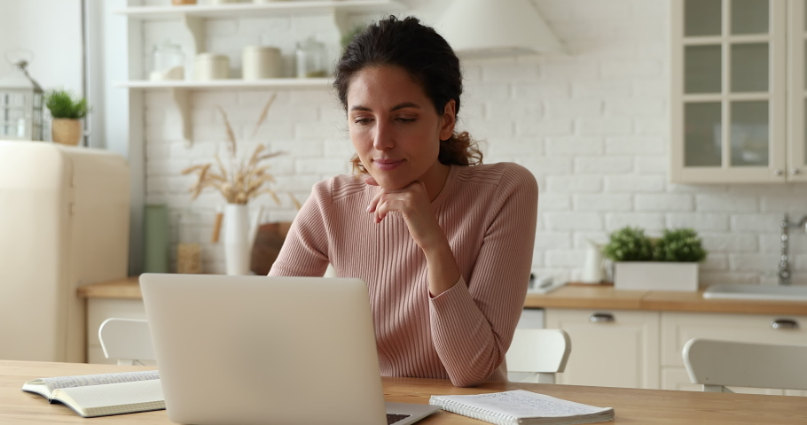 Happy young woman web surfing educational information in internet using computer app, preparing for exams or studying on online courses sitting at table in modern kitchen, writing notes in copybook. Royalty-Free Stock Footage #1066149892