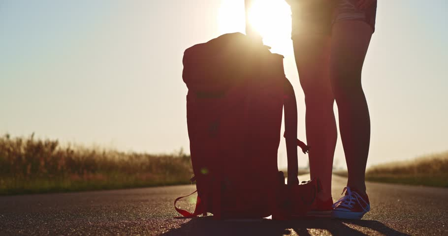 Traveler woman taking off her backpack. Backpacker woman putting her bag down on the road in the morning sunlit background. Lens flare. Slow motion, 120 fps. 4K, DCi. Europe, Poland, Lower Silesia.   | Shutterstock HD Video #10661699