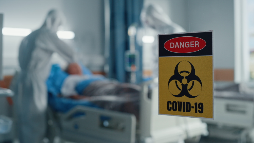 Hospital Coronavirus Emergency Department Ward: Doctors wearing Coveralls, Face Masks Treat, Cure and Save Lives of Patients. Focus on Biohazard Sign on Door, Background Blurred Out of Focus Royalty-Free Stock Footage #1066174411