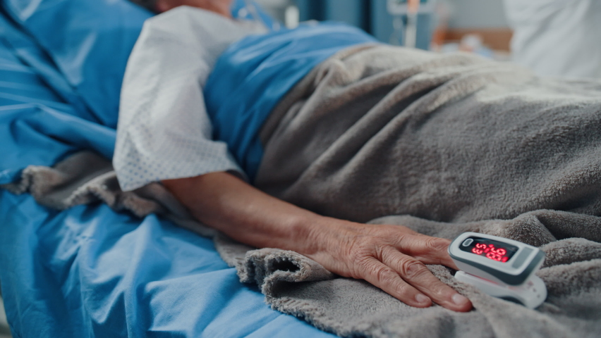 Hospital Coronavirus Emergency Department Ward: Doctor wearing Coverall, Face Mask Writes Down Vitals of Senior Female Patient with Oxygen Mask Resting in Bed. Paramedics Saving Lives. Elevating Shot Royalty-Free Stock Footage #1066174426