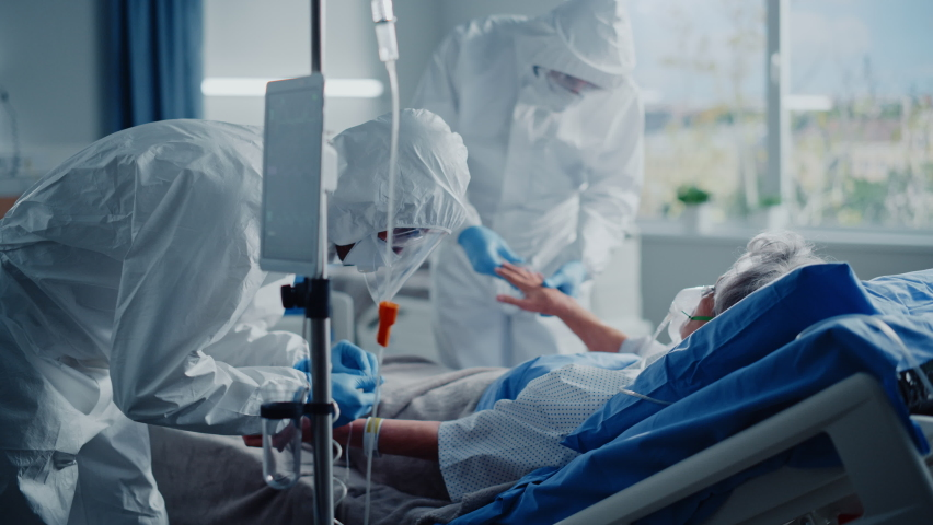 Hospital Coronavirus Emergency Department Ward: Team of Doctors wearing Coveralls, Face Shields Take Care of a Senior Patient Lying in Bed, Put Oxygen Mask and Lung Ventilator. Medics Saving Lives Royalty-Free Stock Footage #1066174459