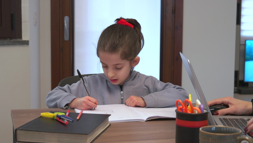 Little girl studying and writing. Young female student doing remote learning. Busy child doing school homework and e-learning during Covid-19 quarantine. Remote education at home   Shutterstock HD Video #1066174732