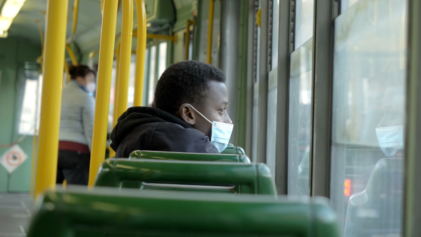 Transport during the covid - young black man wearing the mask sitting on an almost empty bus for fear of contagion | Shutterstock HD Video #1066175719