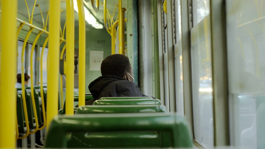 Young black man wearing the mask sitting on the bus away from other passengers | Shutterstock HD Video #1066175728