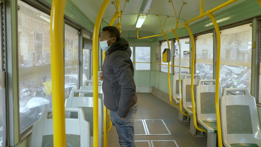Fear of contagion - black man wearing the mask on a empty bus stares at camera | Shutterstock HD Video #1066175731