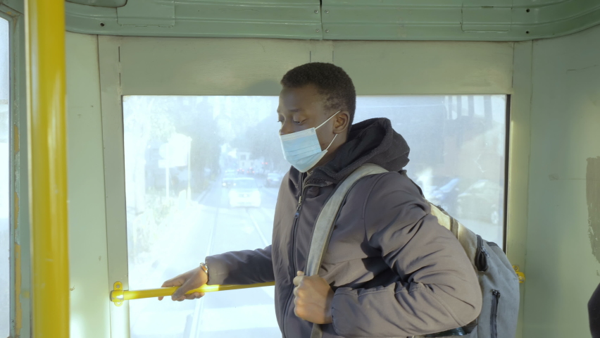 Portrait of young black man wearing in the mask comes home from work by bus | Shutterstock HD Video #1066175737