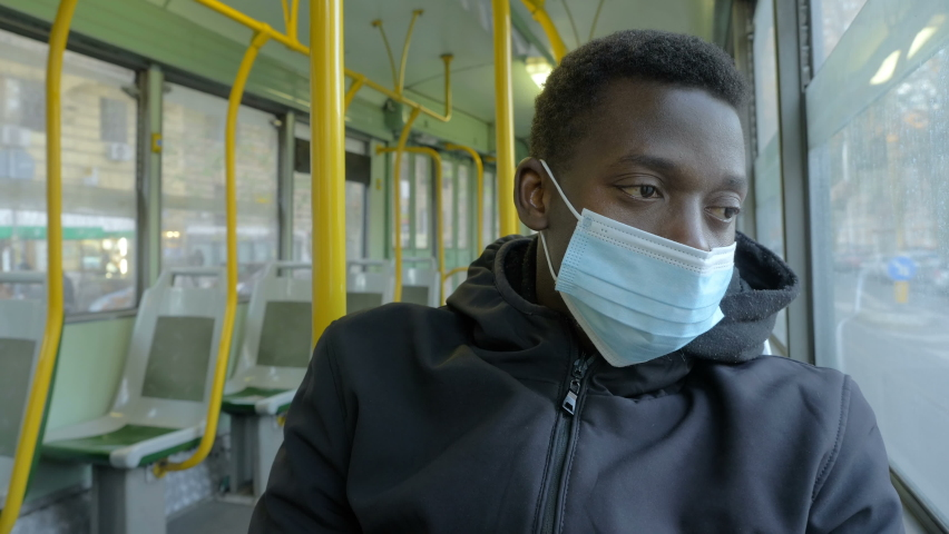 Daily routine - young tired black man wearing the mask uses public transport to get around the city | Shutterstock HD Video #1066175740