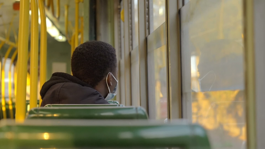Slow motion on young black man wearing the mask looking out the window on a empty bus | Shutterstock HD Video #1066175746