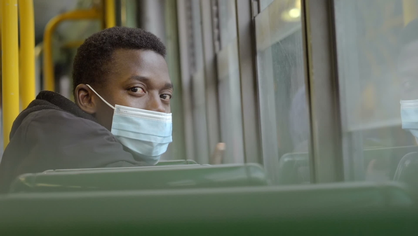 Slow motion on young serious black man wearing the mask sitting on the bus looking at camera | Shutterstock HD Video #1066175752